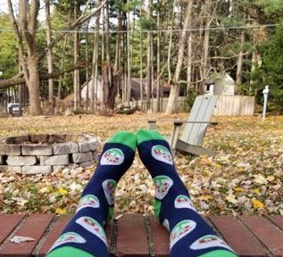 An Orchard employee is showing off their new Orchard socks while sitting outside.